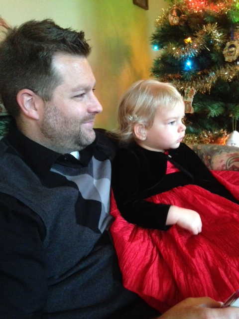 Snuggling with Daddy as she checks out Santa at Kiesewetter Christmas